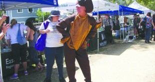 "Billy the Beaver (also known as National Wildlife Federation volunteer Mike Bergstrom) shows off his tail to a curious patron at the 8th annual Beaver Festival, Saturday, Aug. 1, 2015. Bergstrom entertained attendees of the festival as both Billy the Beaver and Ranger Rick Raccoon at ""Beaver Park"" (intersection of Castro and Marina Vista streets) in downtown Martinez. (E. CLARK / Martinez Tribune)"
