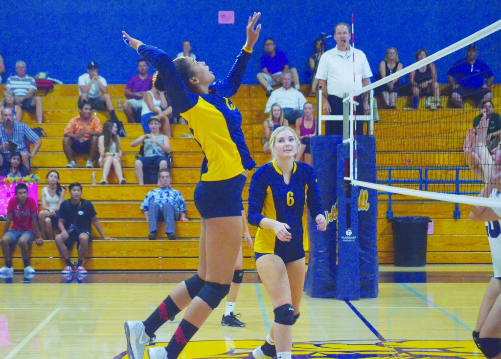Alhambra freshman hitter Sterling Parker rises high as senior Haley Jones looks on in the Bulldogs' 3-1 win over the  sCollege Park Falcons Sept. 9, 2015. (GERARDO RECINOS / Martinez Tribune)