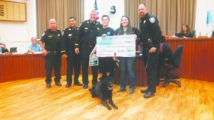 Seth Kozlowski and Lenore Delfino (center), flanked by members of the Martinez Police Department, display a check they presented to the department during the Sept. 16, 2015, City Council meeting. The funds they raised will go towards the purchase of a new K-9, like Logan (front, center). (LAURA DELFINO / Courtesy)