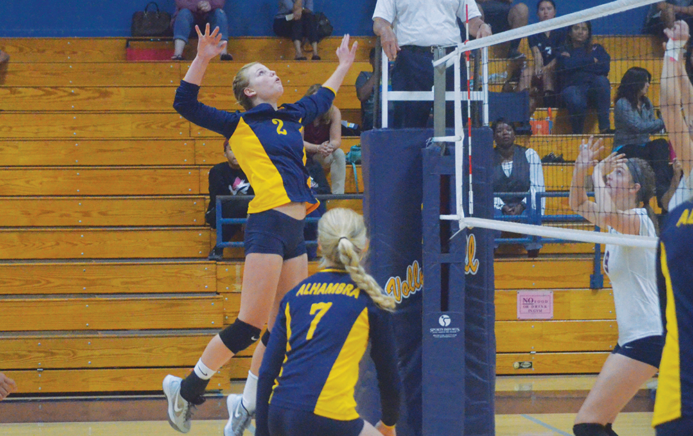 Alhambra sophomore outside hitter Sophia Olson leaps and surveys the court all in one move to place her shot in the Bulldogs' 3-2 loss to the Dublin Gaels on Tuesday, Sept. 29, 2015. Olson had seven kills and three aces in the losing effort. (GERARDO RECINOS / Martinez Tribune)