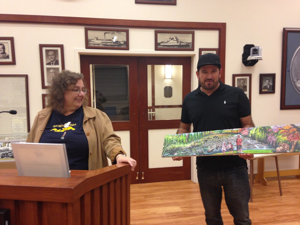 Heidi Perryman (at left) presents Mario Alfaro and his painting of a proposed beaver mural at the Nov. 17, 2015, meeting of the Parks, Recreation, Marina and Cultural Commission. (DONNA BETH WEILENMAN/Martinez Tribune)