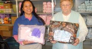 Melanie Toledo (at left) and Newborn Infant Project Chairman Beverly Annis, show examples of completed layettes for the Newborn Infant Project at Contra Costa Regional Medical Center in Martinez. (COURTESY / On File)