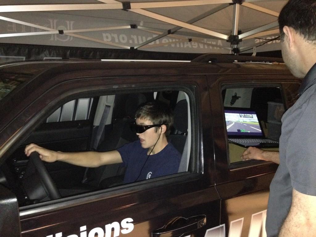 Simulator operator Kent Tiedeman (far right) monitors Bryan Goetze's erratic driving in the Arrive Alive simulator last week at Alhambra High School. (DONNA BETH WEILENMAN / Martinez Tribune)