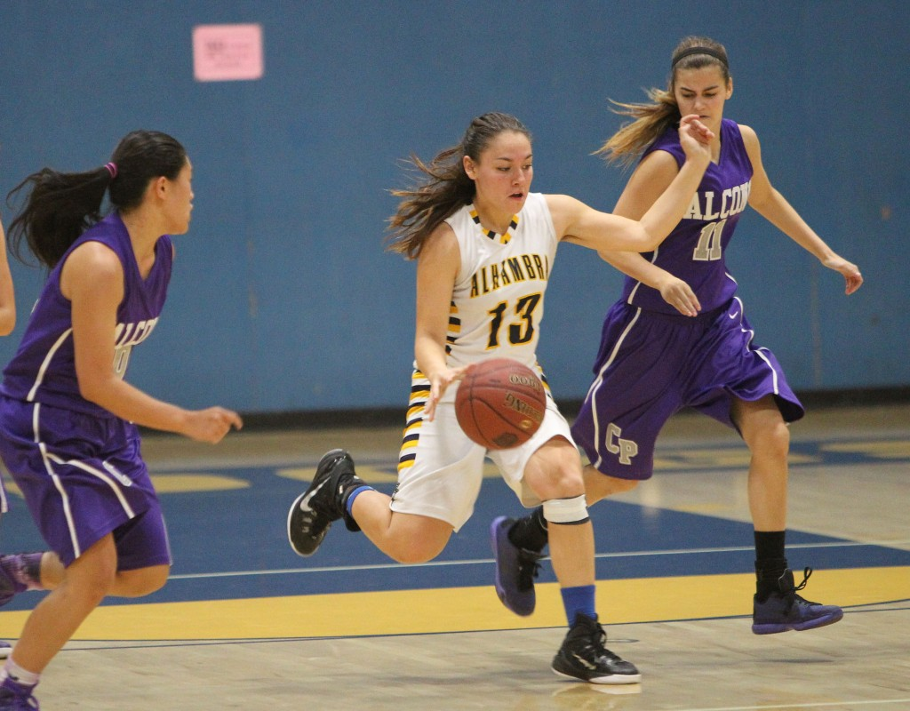 Alhambra junior guard Alanis Lara dribbles between two College Park defenders in the Bulldogs' 50-42 loss to the rival Falcons on Friday, Dec. 4, 2015. Lara scored 10 points in the loss. (MARK FIERNER/ Martinez Tribune)