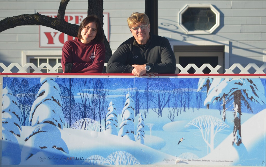 John Kleber (at right) of ARTU4iA and art student Hannah de Vries, stand in front of a dasher board at the ice rink in downtown Martinez. Martinez's premier artist, Kleber illustrated the dasher board – sponsored in part by the Martinez Tribune – as a holiday gift to the community. An accomplished ice skater himself, Kleber said he was inspired by memories of his youth, having learned to skate in a setting very much like the one seen on this dasher board. Visitors to the ice rink on Ferry Street may get an up-close view of the piece from either the rink or the viewing platform just outside (see Page 4 for hours of operation). For more information on Kleber, visit www.artu4ia.com. (GERARDO RECINOS / Martinez Tribune)