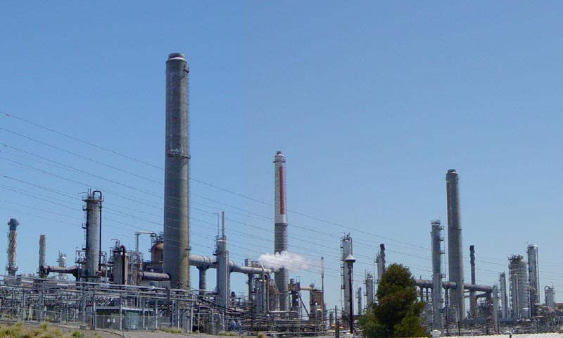 The Shell Martinez oil refinery in Martinez, California. The tapering vertical elements are smokestacks to create draft for heating units. Most of the complex vertical units are fractionating towers. Others are flares. (WIKIMEDIA COMMONS)