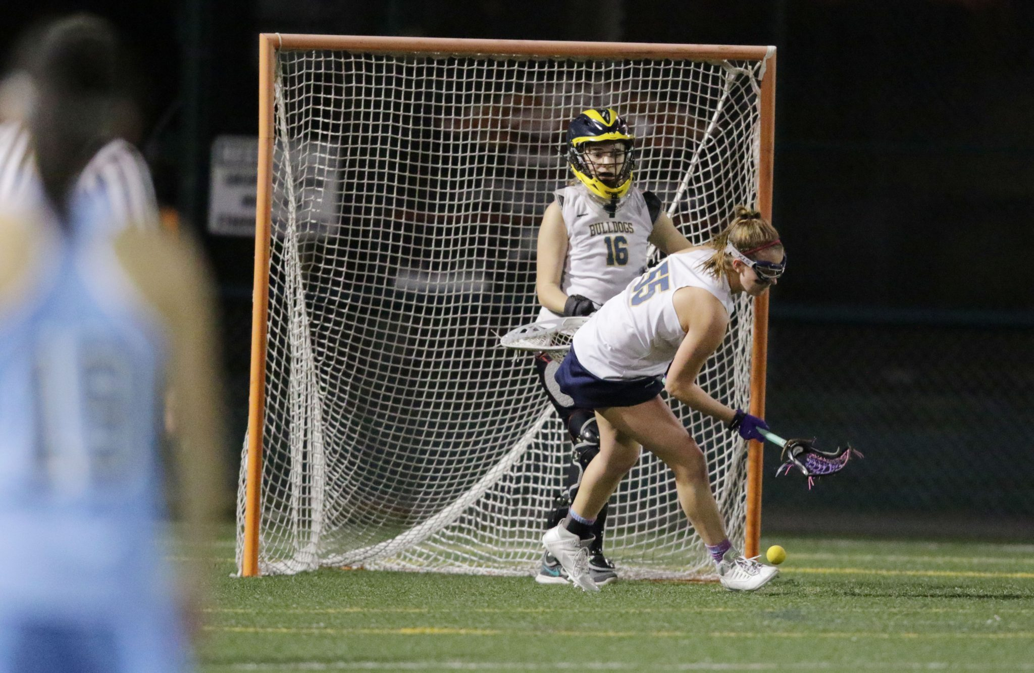 Alhambra's Theresa Hansen (16) watches on as teammate Daria Dragecevic clears a ground ball in front of goal in the Bulldogs' 19-3 loss to the Dougherty Valley Wildcats on Friday, March 25, 2016. The Wildcats are ranked 99th in the nation according to MaxPreps.com, and are currently in first place in the Diablo Foothill Athletic League with an undefeated record. (MARK FIERNER / Martinez Tribune)