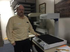 President of the Contra Costa County Historical Society, Scott Saftler, stands next to one of the $15,000 scanners the Center uses to digitize historical documents and photographs. (TASHINA MANYAK / Martinez Tribune)