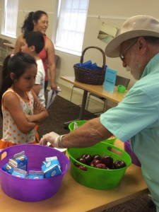 "A local volunteer serves a child during a recent ""Lunch at the Library"" program. (RUTH BOYER / Courtesy)"