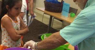 """A local volunteer serves a child during a recent """"Lunch at the Library"""" program. (RUTH BOYER / Courtesy)"""