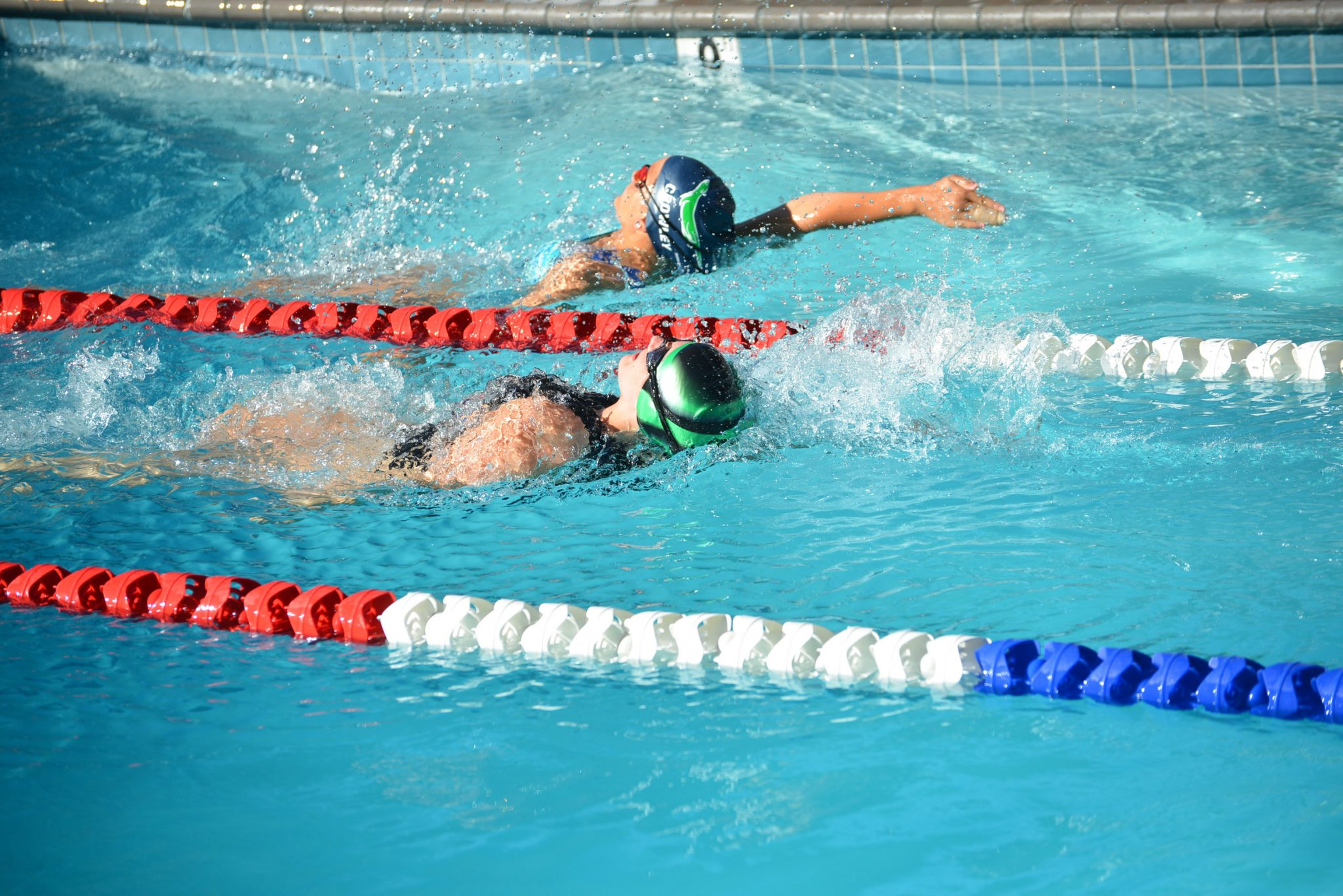 Sydney Leonard from Forest Hills and Rowan Crowley from MCST compete neck and neck in the water. (COURTESY / On File)