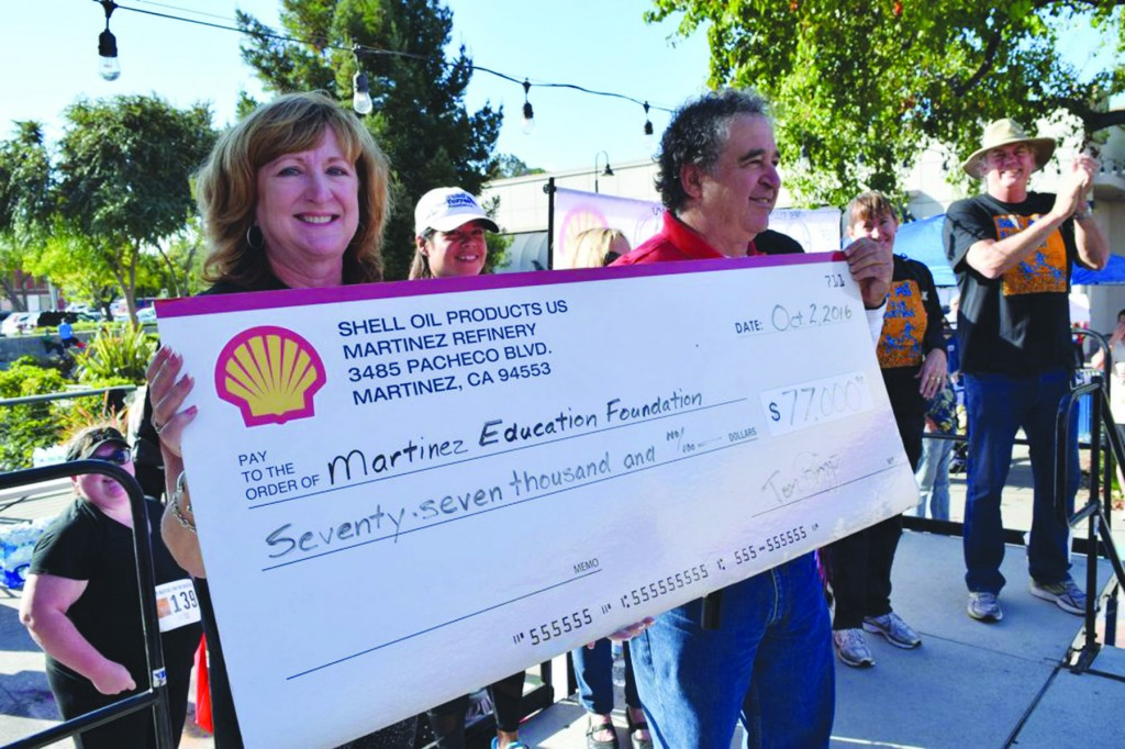 Cheryl Vereschagin, president of the Martinez Education Foundation, accepts a check for $77,000 raised in the 2016 Shell/MEF Run for Education from Shell Martinez Refinery General Manager Tom Rizzo. (SHELL MARTINEZ REFINERY)