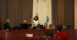 Mayor Rob Schroder (at left) presents Councilmember AnaMarie Avila Farias with an engraved crystal vase as her children look on. Avila Farias received the vase during the Dec. 7, 2016, meeting of the Martinez City Council, in recognition of her public service. The evening marked Avila Farias' last time on the dais, this term, as a retiring councilmember. (E. CLARK / Martinez Tribune)