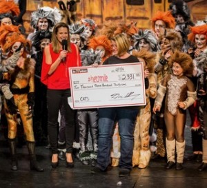 Deena Roming (at left) presents a check to HerSmile director, Dena Betti, during the final performance of Cats on Dec. 17, 2016. (COURTESY / On File)