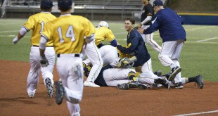 Alhambra's baseball team mobs reliever Marshall Stanghellini after his ground ball in the bottom of the eighth inning drove in the winning run in the Bulldogs' 4-3 win over Pittsburg High School in the semi-finals of the Easter Tournament. Stanghellini also went five shutout innings in relief to keep the Bulldogs in the contest. (MARK FIERNER / Martinez Tribune)