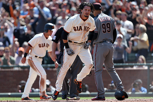 ©DANIEL GLUSKOTER San Francisco's  Jarrett Parker bounces up at the plate after scoring all the way from first on  Matt Moore's dribbler during a 4-1  win over Arizona Monday in the Giants home opener.