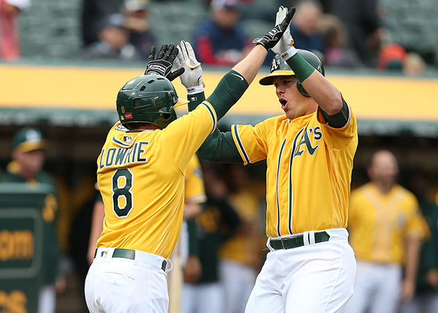 ©Daniel Gluskoter Ryon Healy is greeted at home by Jed Lowrie following his fourth inning home run at the Coliseum on Thursday during the A's 5-1 win over the Angels.