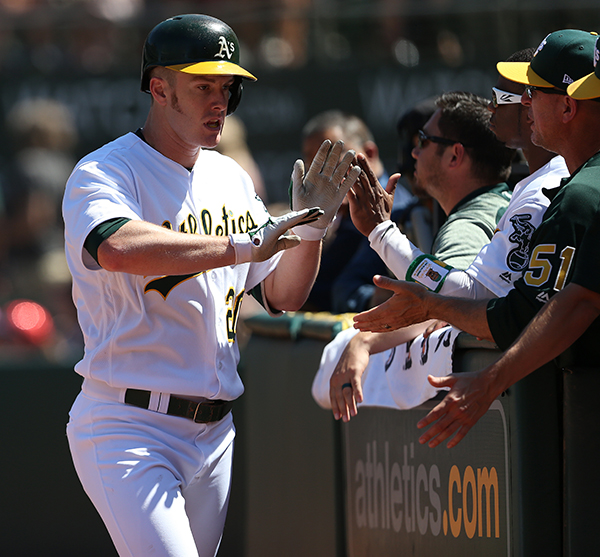 ©DANIEL GLUSKOTER Mark Canha received congratulations after blasting a 453 foot home run against the Red Sox on Saturday. Canha also hit a tenth inning walk off the night before as the A's took three ion four from Boston.