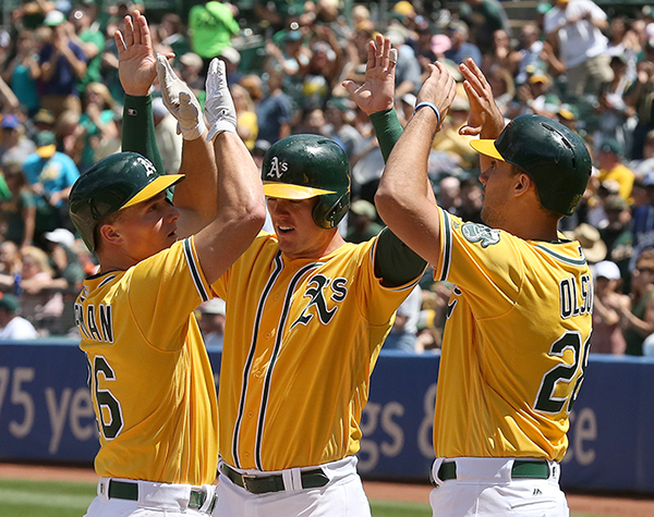 ©DANIEL GLUSKOTER Oakland's Matt Chapman is greeted at homeplate by Ryan Healy and Matt Olson following his three run home run on Sunday during the A's 9-3 win over the Baltimore Orioles.