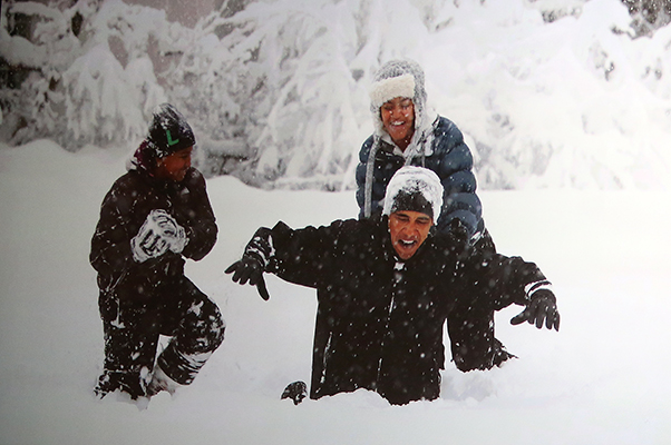 ©PETE SOUZA Former President Barack Obama plays in the snow with his then young daughters on the White House lawn.