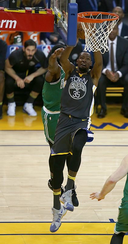 ©DANIEL GLUSKOTER Kevin Durant goes up for a dunk in front of Jaylen Brown during the Warriors 109-105 win over the Boston Celtics at Oracle Arena Saturday night.