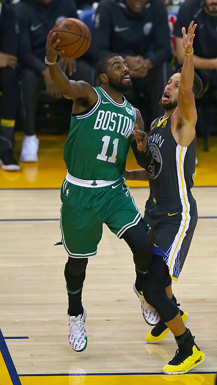 ©DANIEL GLUSKOTER Boston's Kyrie Irving gets off a pass over Steph Curry during the Warriors 109-105 win Saturday night. Irving led the Celtics with 37 points.