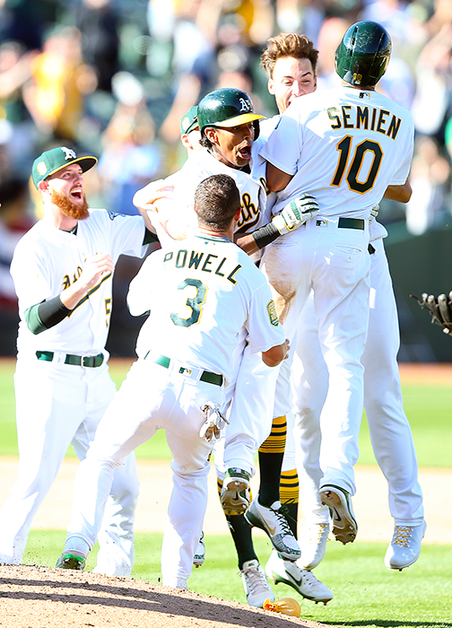 ©DANIEL GLUSKOTER Marcus Semien gets embraced by Khris Davis (center) and others following his 11th inning walk-off single during the A's 6-5 season opening win on Thursday at the Oakland Coliseum. Davis had four RBI's, including a three run  homer in the fifth, to put the A's in a position to win.