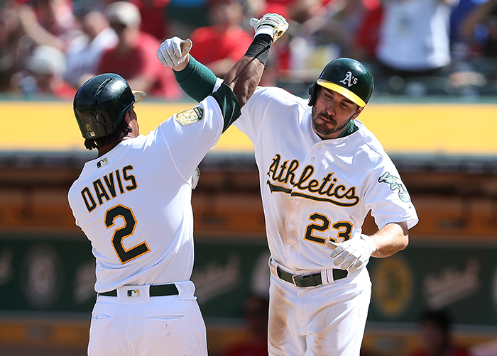 ©DANIEL GLUSKOTER Khris Davis is greeted at home by Matt Joyce (23) following his three run fifth inning home run during Thursday's season opening win in Oakland.